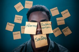 """A man with sticky notes around him with words like """"Norms"""" and """"Expectations"""" written on them"""