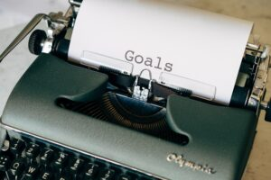 A typwriter with paper on it that has the words 'GOAL' printed on them