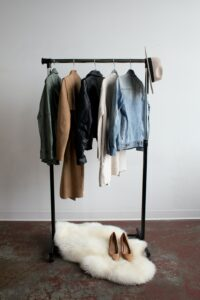 A wardrobe of clothing hanging on a rack
