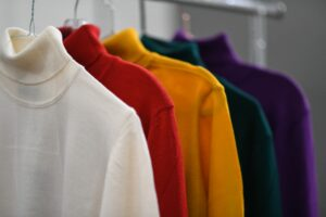A bunch of different colored shirts hanging on a rack