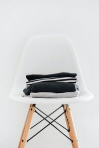 A minimalistic amount of clothes folded neatly on a chair