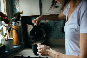 A woman pouring out her morning coffee routine