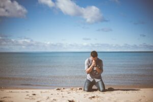 A man praying and crying by the seashore