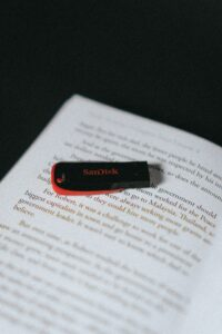 A flashdrive on top of a book to signify that you can put that book on something electronic