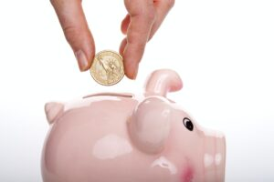 A person putting a coin in a piggy bank to save money