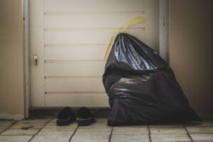 A trash bag full of trash in front of a door