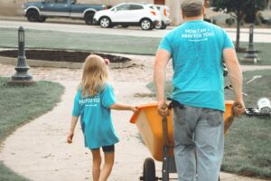 A Man And His Daughter Volunteering At A Service Project