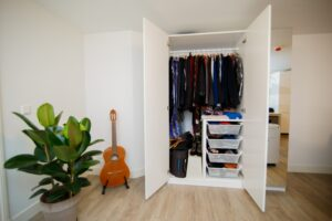 An open wardrobe with clothing in it, signifying someone building their own capsule wardrobe.